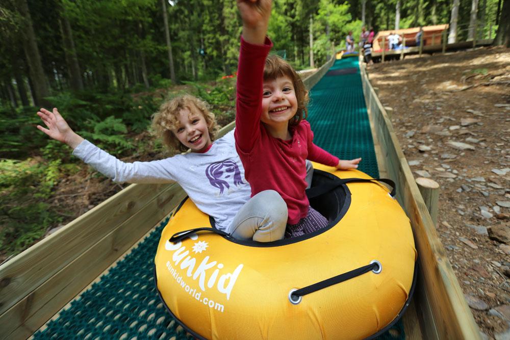Photographie d'enfants jouants dans une luge d'été prise à elfy park par Yauque Company